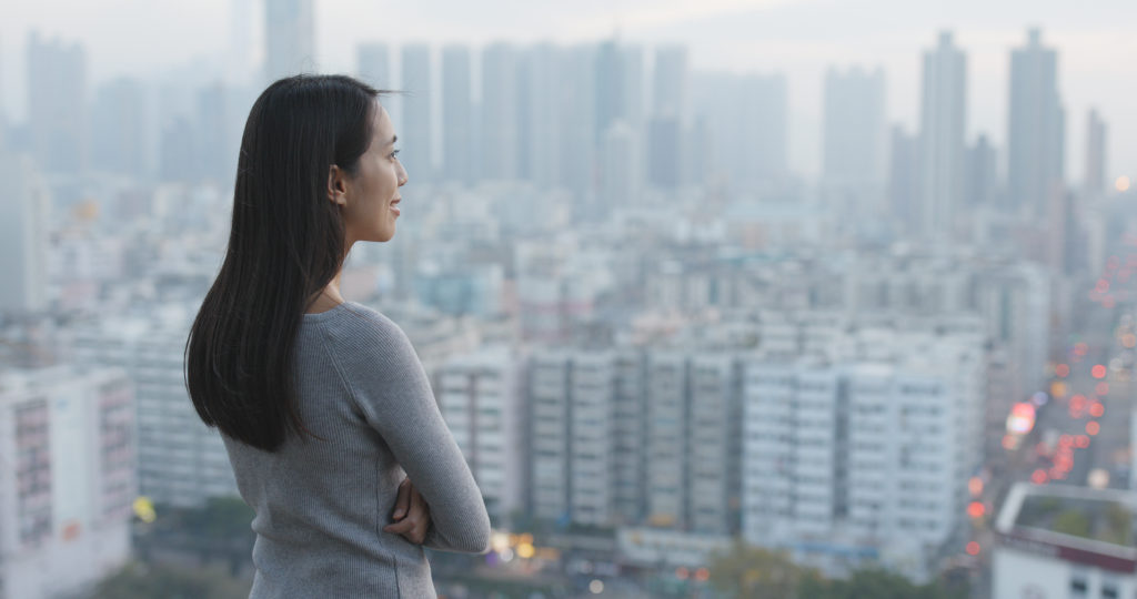 Chinese woman staring out over the city
