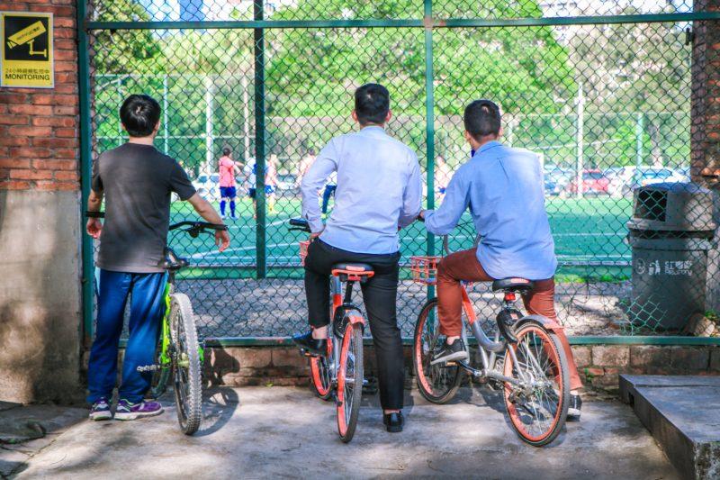 Cyclists watch football in China. Credit: Unsplash